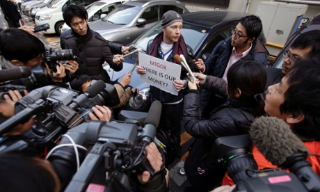 Bitcoin trader Kolin Burges is surrounded by press photographers and reporters during his protest outside an office building housing Mt. Gox in Tokyo, Wednesday, Feb. 26, 2014.