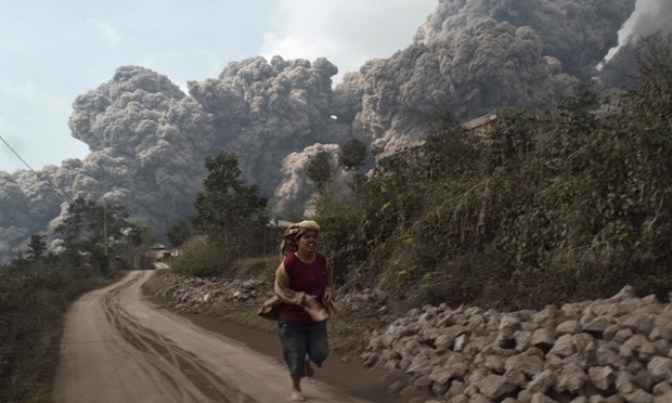 A villager runs as Mount Sinabung erupts at Sigarang-Garang village in Karo