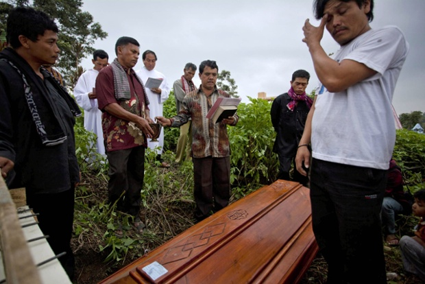 Relatives pray during the burial of a victim who was killed after being hit by pyroclastic smoke from the eruption of Mount Sinabung.