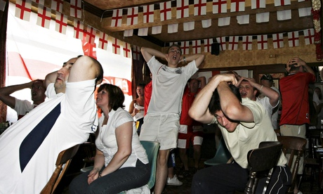 English football supporters watch a game in a pub