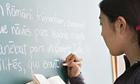 Girl writing latin on blackboard