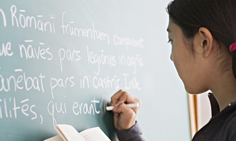 Girl writing latin on blackboard