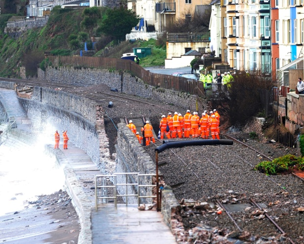 Engineers and members of the emergency services  survey the sunken section of the mainline railway track near Dawlish, Devon.