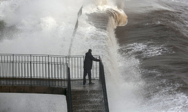 A man watches as waves crash against the seafront and the railway line that has been closed due to storm damage at Dawlish.