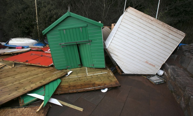 Beach huts are damaged by the storm waves at Dawlish.