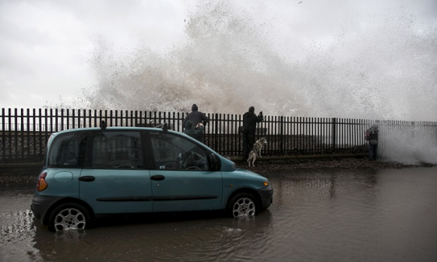 People take photographs as waves crash against the seafront at Dawlish.