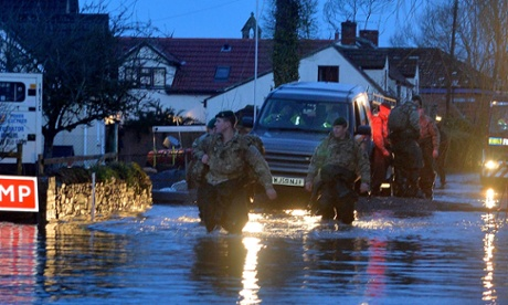 Royal Marines lead volunteers and fire services through Moorland on the Somerset Levels early on Friday