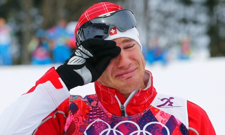 Winner Dario Cologna of Switzerland is moved to tears during the flower ceremony for the men's skiathlon.