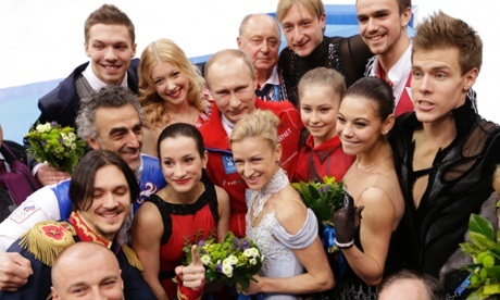Russian President Vladimir Putin poses with the Russian team after they won the team figure skating competition at the 2014 Winter Olympics.