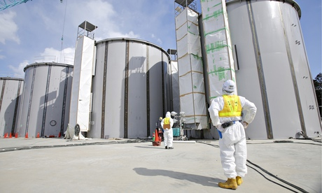 A worker in a protective suit looks at tanks, under construction, to store radioactive water