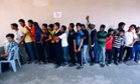 Rohingya men stand in a line at a centre to register for a temporary card issued by the United Nations High Commissioner for Refugees (UNHCR) in Kuala Lumpur.