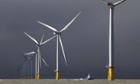 A boat passes between wind turbines at the London Array project, the world's largest windfarm