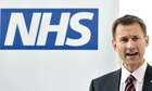 Jeremy Hunt speaking in front of big NHS logo