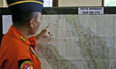 An Indonesian air force officer with map of Strait of Malacca in the search for the missing plane
