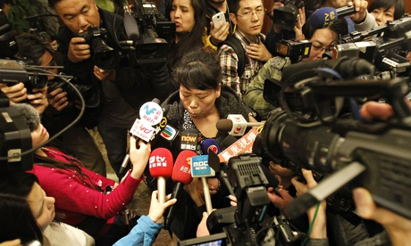 A relative of a passenger on the missing MH370 answers media questions in Beijing