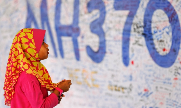 A girl looks at a board with messages of support and hope for passengers of the missing Malaysia Airlines plane at Kuala Lumpur international airport.