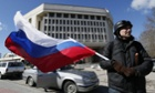A man holds a Russian flag as he stands in front of the Crimea's parliament in Simferopol, Crimea, Ukraine, 17 March 2014.