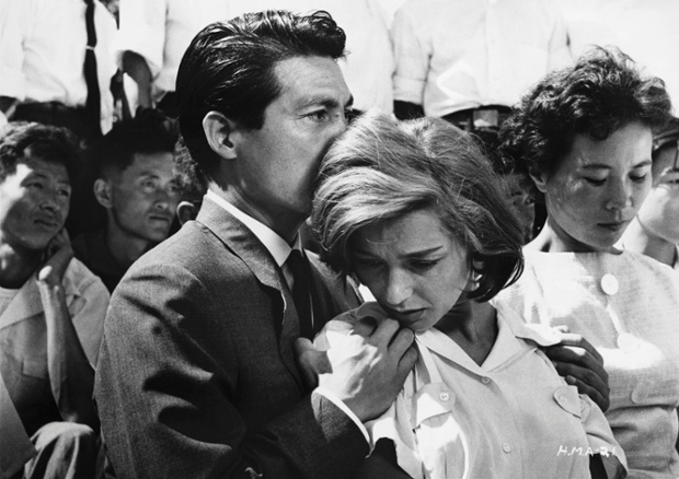 1959: Lui (Eiji Okada) holds Elle (Emmanuelle Riva) in a crowd in a scene from film Hiroshima Mon Amour.