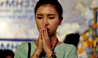 A woman prays for the missing of flight MH370