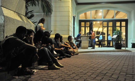 Journalists wait in front of the guarded entrance of the hotel where Chinese relatives of passengers on the missing Malaysia Airlines flight MH370 stay.