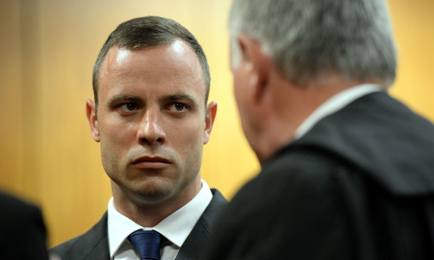 Oscar Pistorius talks with his lawyer Barry Roux during his ongoing murder trial on March 24, 2014 in Pretoria.