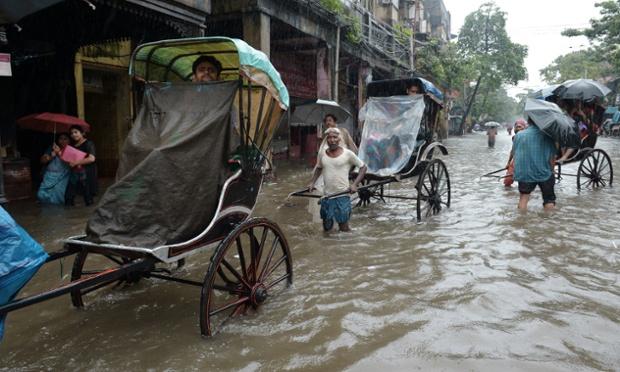 Rickshaw pullers carry passengers through water-logged streets in Kolkata