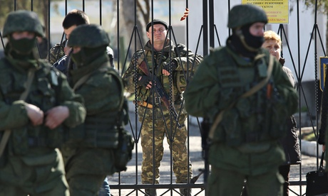 A Ukrainian soldier in a Ukrainian base in Crimea as unidentified (Russian) soldiers encircle it
