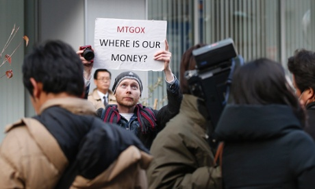Kolin Burges, a self-styled cryptocurrency trader and former software engineer from London, holds up a placard to protest against Mt. Gox.