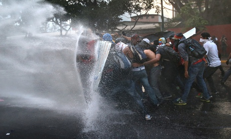 Venezuela protesters hold a barricade against a water canon fired by the National Guard