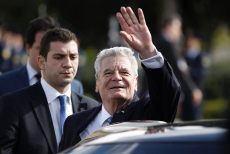 German President Joachim Gauck waves to onlookers following a wreath laying ceremony at the Tomb of the Unknown Soldier in Athens' Syntagma Square March 6, 2014.