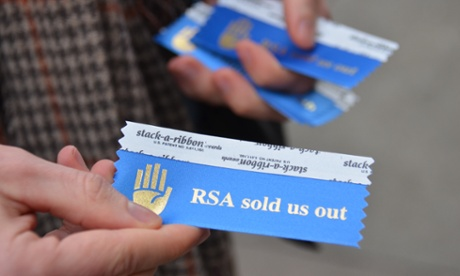 A man hands out 'RSA sold us out' ribbons near Moscone West for the badges of people attending the RSA conference.