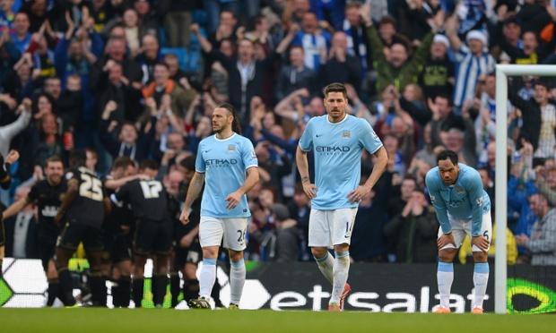Joleon Lescott, Martin Demichelis and Javi Garcia look dejected as Wigan celebrate the second goal.