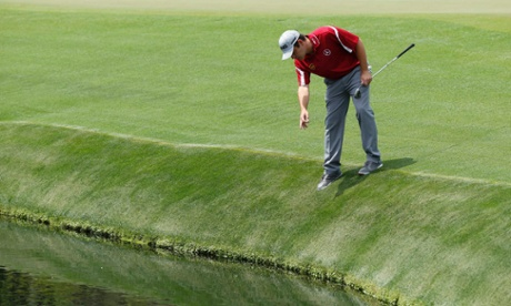 Louis Oosthuizen looks for his ball in the water.