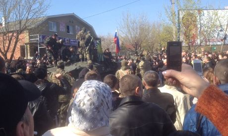 Crowds look on as pro-Russian separatists drive round the city on armoured vehicles
