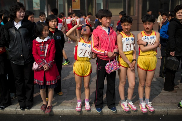 Young North Korean runners rest after finishing