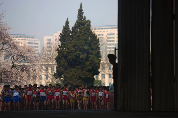 Young North Korean runners stand ready outside Kim Il Sung Stadium