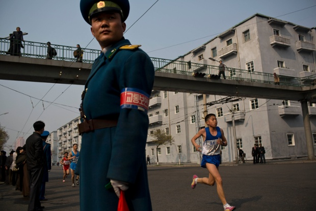 Runners pass under a pedestrian bridge in central Pyongyang