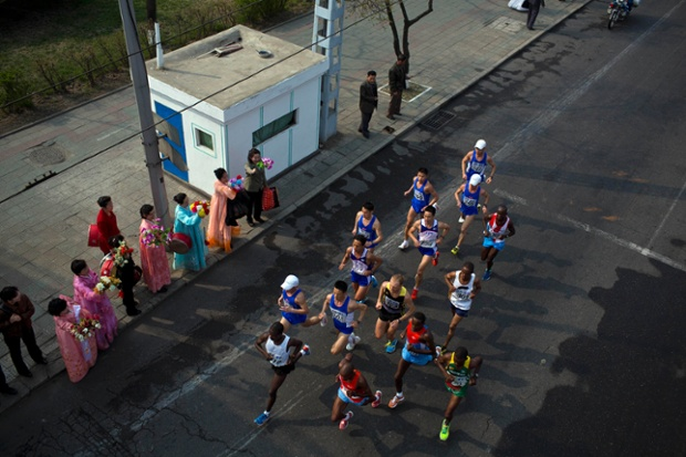 The lead pack of runners are cheered on by North Korean spectators on the roadside