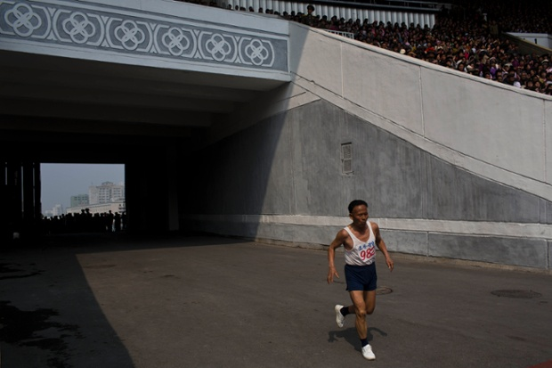 An elderly North Korean man enters Kim Il Sung Stadium at the last stretch of his run