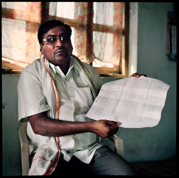 Vinod Kale, the head of Kalamb village holds up a list of all the cotton farmers who have commit suicide in his village