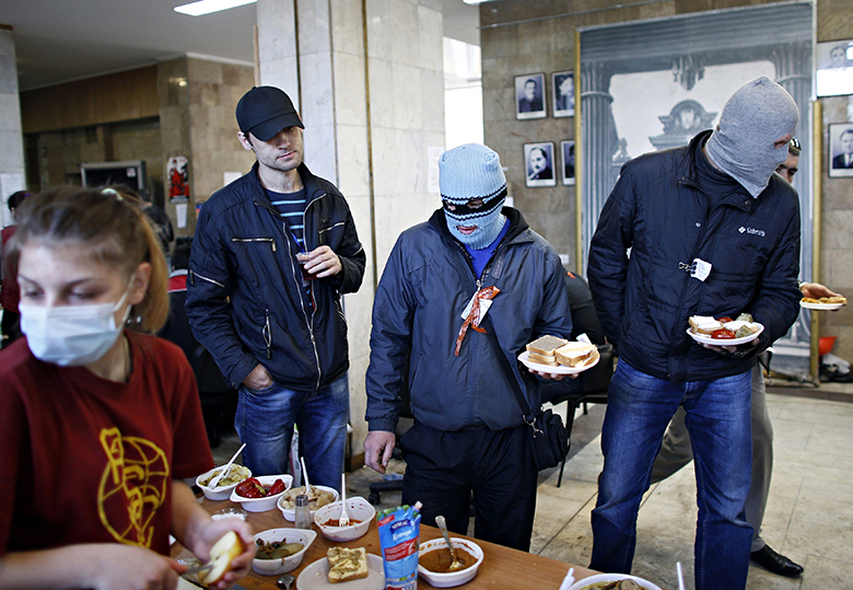 Masked pro-Russia protesters in a queue for food inside a regional government building in Donetsk