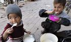 Two children eat food distributed to them in the besieged Yarmouk refugee camp.