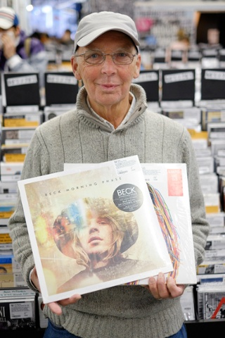Ken Morcombe, 75, from Croydon poses with his purchases (these ones were presents for his grandson) : Morning Phase by Beck and Mess by Liars.