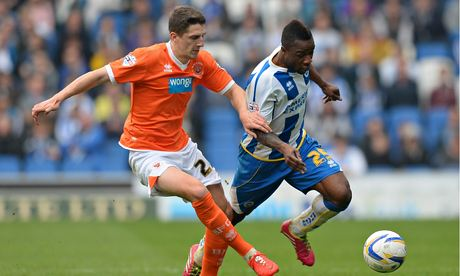 The Brighton & Hove Albion wing Kazenga LuaLua, right, is challenged by Blackpool's Craig Cathcart