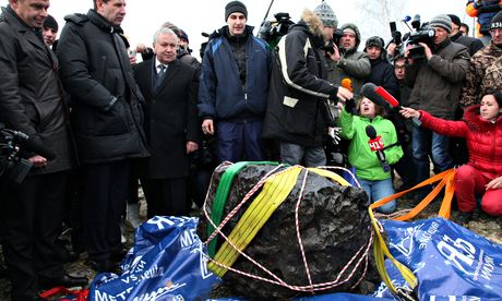 People look at what is believed to be a chunk of the Chelyabinsk meteor in Russia in 2013