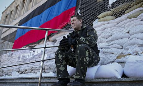 A pro-Russian armed man guards the mayor's office in Slavyansk on Friday