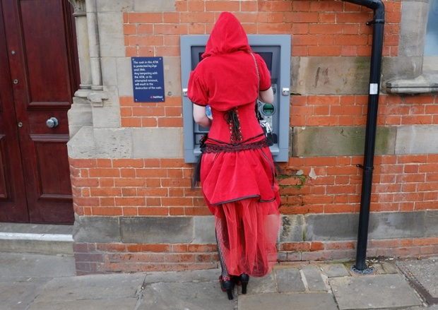 A woman dressed a Little Red Riding Hood withdraws money from a cashpoint. ~ Getty Photograph by Ian Forsyth