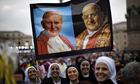 Nuns among the 800,000 pilgrims hold up portraits of Pope John Paul II, left, and Pope John XXIII