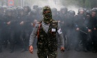 A pro-Russian activist walks in front of Ukrainian riot police during a pro-Ukrainian rally in the eastern city of Donetsk April 28, 2014.