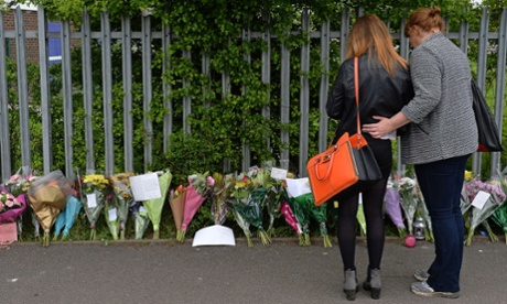 A woman and child look at floral tributes left at Corpus Christi Catholic College in Leeds, northern England, on April 29, 2014, following the fatal stabbing of a teacher Anne Maguire by a pupil Monday.